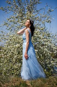 晴れた暖かい夏の日に彼女の顔に笑顔で咲く桜の下にチュールと青いロングドレスの優しい女の子の肖像画