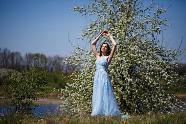 화창한 여름날 그녀의 얼굴에 미소를 지으며 꽃이 만발한 체리 아래 얇은 명주 그물이 있는 파란색 긴 드레스를 입은 부드러운 소녀의 초상화