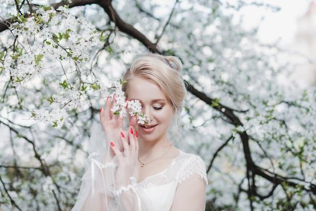 Портрет нежной молодой невесты. красивая чувственная молодая блондинка невеста в цветущем саду