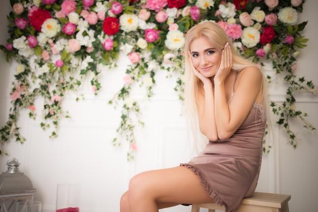 Портрет нежной молодой красивой блондинки, позирующей на расплывчатых ярких цветах цветов и белой стене.
