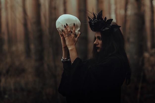 죽은 남자의 손에 두개골이 있는 끔찍한 마녀의 초상화는 숲에서 신비로운 신비로운 의식을 수행합니다