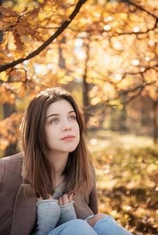 思いやりのある悲しい少女の肖像画。秋の色。ライフスタイル。秋の気分。森