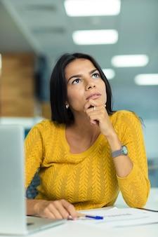 Портрет вдумчивой бизнес-леди, сидящей за столом в офисе