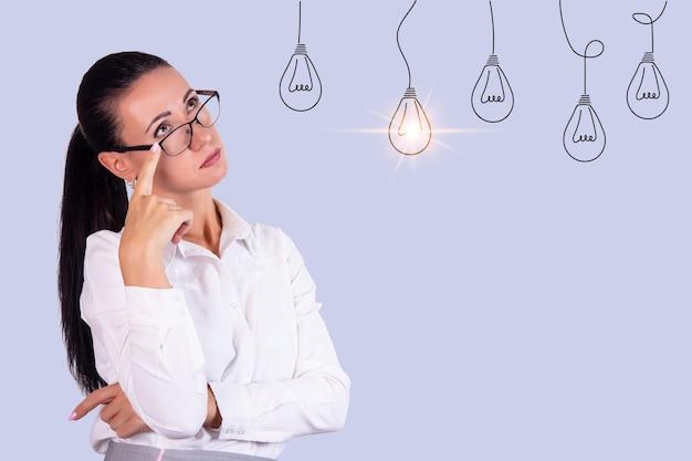 전구를 아이디어로 보고 있는 안경을 쓴 사려 깊은 젊은 비즈니스 여성의 초상화. 공간을 복사합니다. 고품질 사진