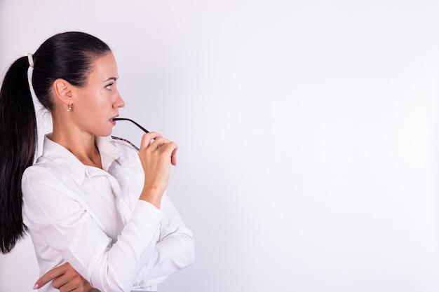 白い壁に隔離された空間を見て眼鏡をかけて思慮深い若い女性の肖像画