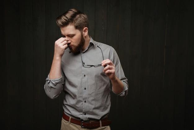 Портрет усталого, измученного бородатого мужчины, держащего очки и смотрящего в сторону, изолированного на черной деревянной поверхности