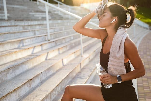 Портрет усталой фитнес женщины с полотенцем