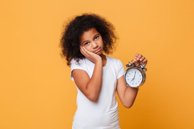 目覚まし時計を保持している疲れの小さなアフリカの女の子の肖像画