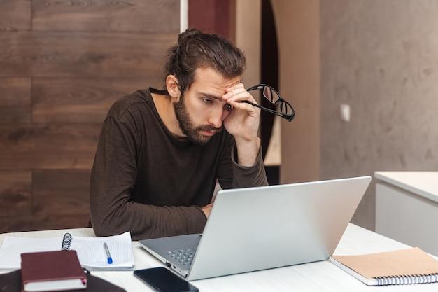 疲れたプログラマーの肖像画。コンピューターで働いているひげを持つ悲しい男