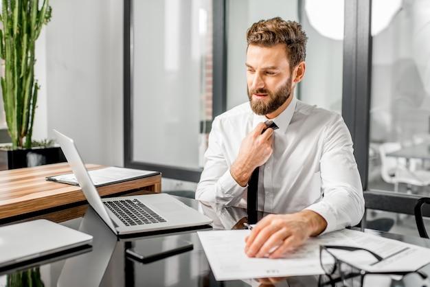 オフィスで税務書類とラップトップを操作しながらネクタイを脱いで疲れた税務マネージャーの肖像画