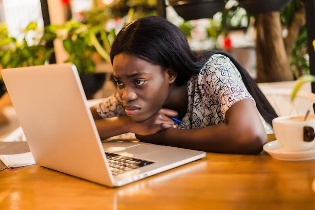 カフェで寝ている間ラップトップコンピューターでテーブルに座っている疲れた若いアフリカの女性の肖像画