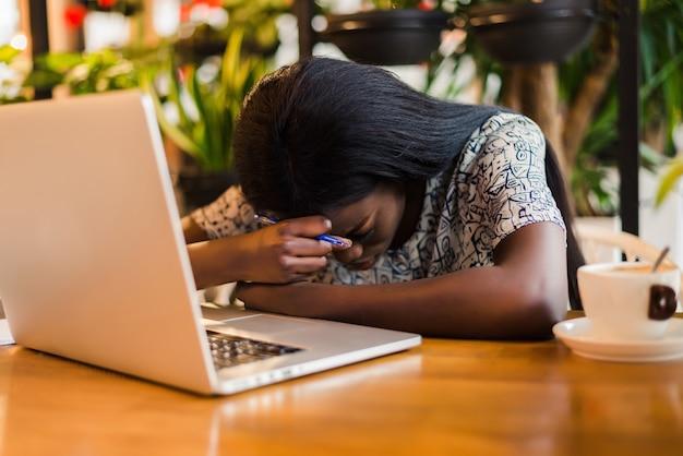 카페에서 자고있는 동안 노트북 컴퓨터와 함께 테이블에 앉아 피곤 젊은 아프리카 여자의 초상화