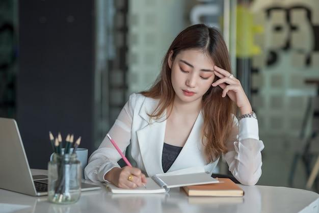 사무실에서 노트북 컴퓨터와 함께 테이블에 앉아 피곤 된 젊은 아시아 사업가의 초상화.