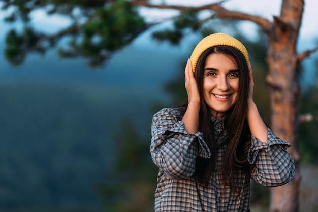 Портрет девушки путешественницы в желтой кепке. портрет туристки. девушка улыбается и смотрит в камеру. девушка туристка. копировать пространство