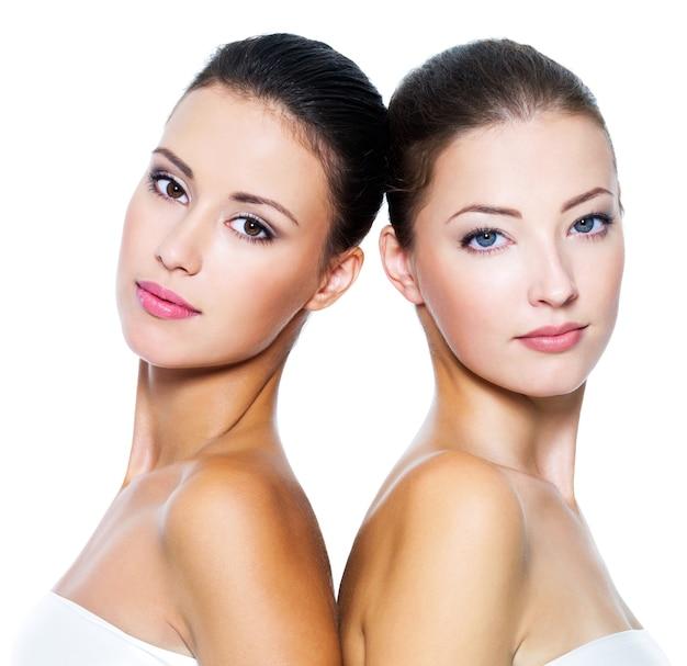 Портрет двух красивых молодых женщин, изолированных на белом