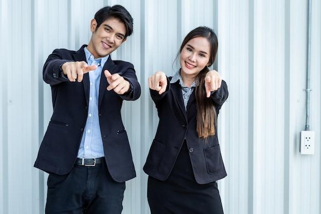 매력적인 긍정적인 사업에 대해 두 손과 손가락으로 가리키는 두 사업가 및 사업가 파트너의 초상화는 자신감을 대담하고 성공적인 개념으로 표현했습니다.