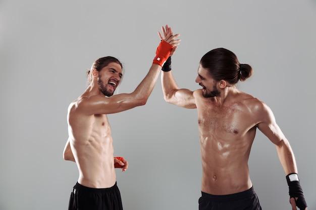 2人の自信を持って筋肉質の上半身裸の双子の兄弟の肖像画