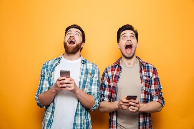 Портрет двух возбужденных молодых людей с мобильными телефонами