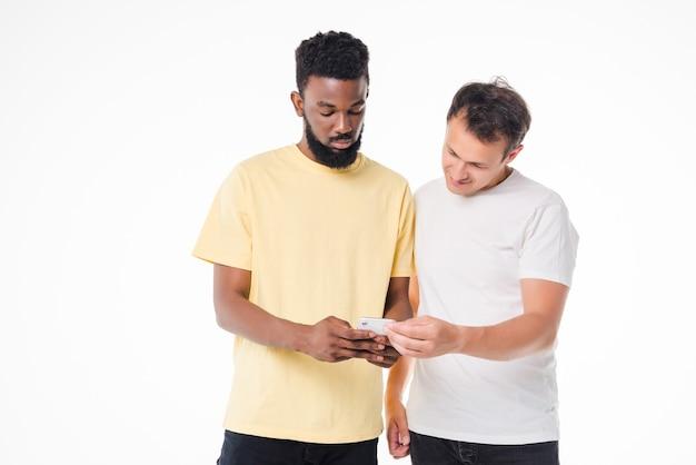 白い壁に隔離されたスマートフォンを使用して2人の幸せな男性の肖像画