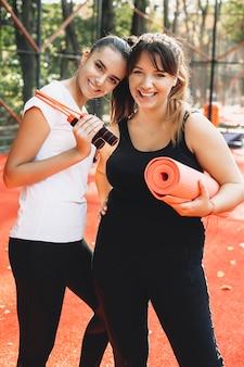 Портрет двух прекрасных молодых женщин, смотрящих на камеру, смеясь перед утренней растяжкой на улице в спортивном парке.
