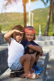 두 미취학 아동의 초상화입니다. 운동복을 입은 즐거운 소년은 스케이트보드에 여동생과 함께 앉아 이마에 손을 얹고 카메라를 쳐다봅니다.