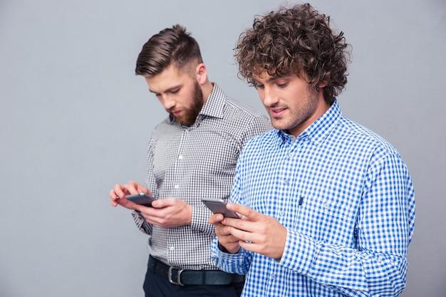 Портрет двух серьезных мужчин, использующих смартфон над серой стеной