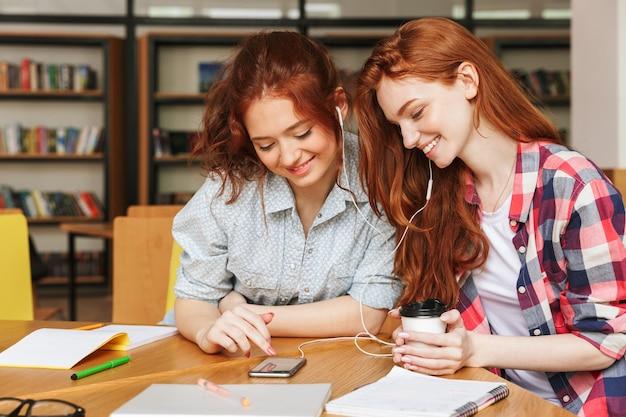 音楽を聴く2人の笑顔の10代の少女の肖像画