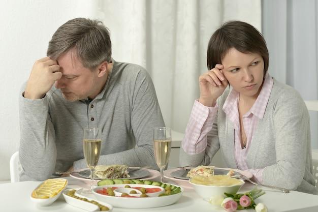 不幸なカップルの肖像画は、レストランで夕食をとります