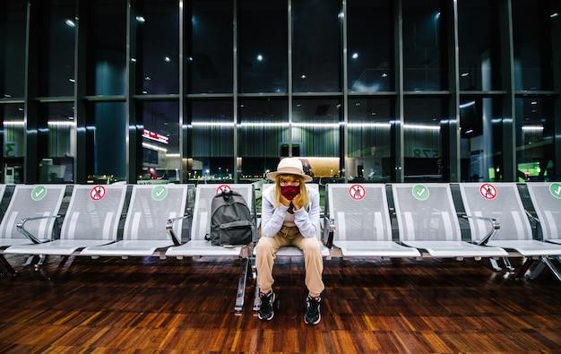 空港でcovid19から保護するためにフェイスマスクを身に着けている不幸な観光客の女性の肖像画。