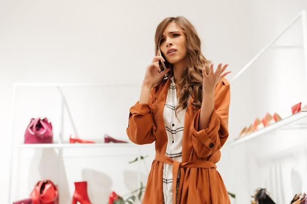 Портрет расстроенной женщины разговаривают по мобильному телефону