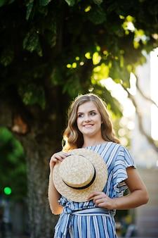 町の舗装に帽子をかぶって全体的にストライプのポーズで非常に魅力的な若い女性の肖像画