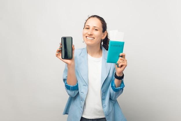 활짝 웃는 여성의 초상화가 그녀가 가지고 있는 전화와 여권을 카메라에 보여주고 있습니다.
