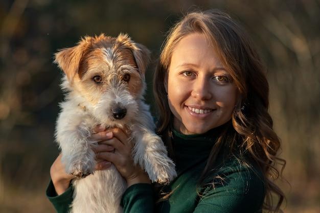 철사 머리 잭 러셀 테리어 강아지와 가을 공원에서 녹색 드레스를 입은 소녀의 초상화