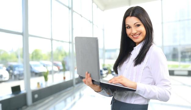 Портрет женщины-администратора с ноутбуком в офисе
