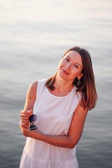 Портрет женщины на закате счастливая милая женщина позирует на закате, держа солнцезащитные очки у моря на ...