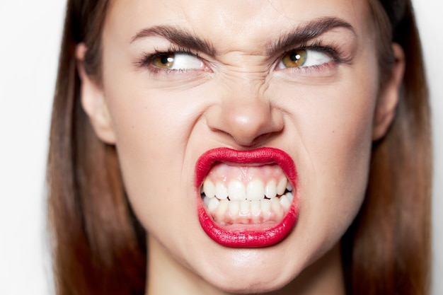 Портрет женщины скалит зубы и смотрит в сторону с гримасой эмоций