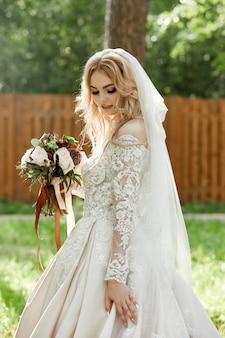 彼女の手に花束を持つウェディングドレスの女性の花嫁の肖像画
