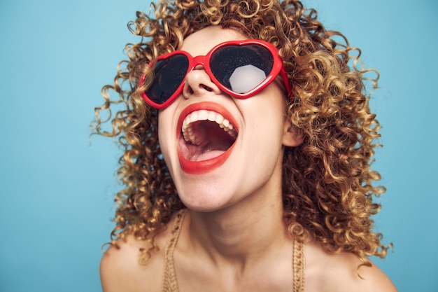 Портрет женщины вьющиеся волосы весело крупным планом красные сердца очки яркий макияж синий изолированный фон