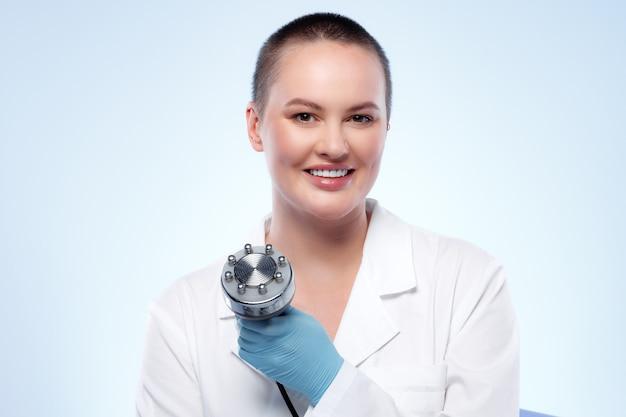 Портрет женщины-дерматолога, держащей насадку для косметического устройства