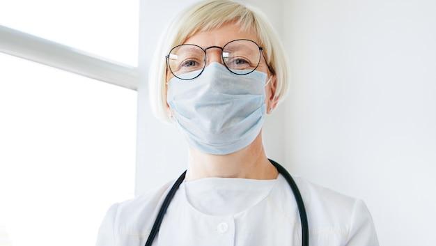 カメラを見ている医療マスクの女医の肖像画。ヘルスケア、医療の概念。家族療法士
