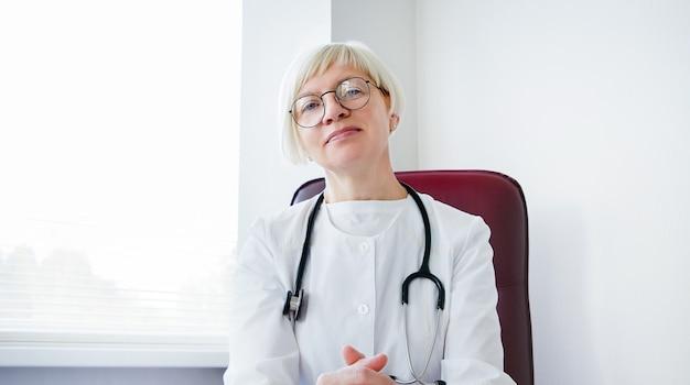 カメラを見て女性医師の肖像画。オフィスのテーブルで家族セラピスト。