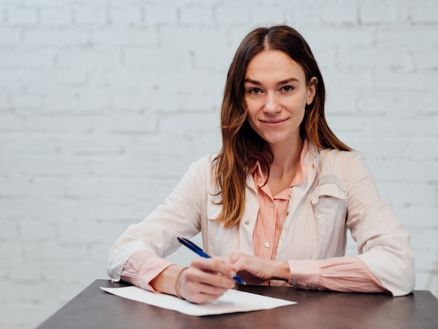 ペンと紙で彼女の机に座っている女性医師の肖像画。