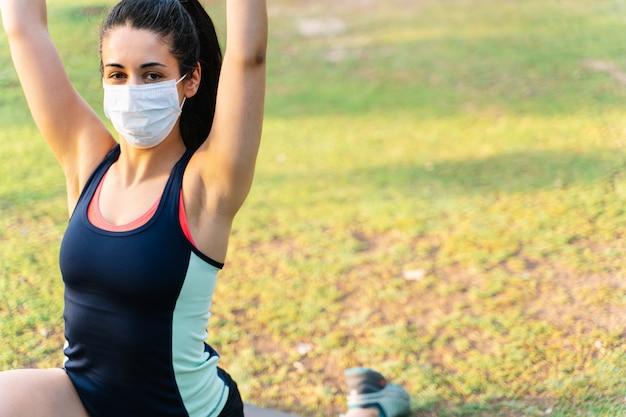 Портрет женщины делая представление йоги в парк пока носит маску. новая концепция нормальности