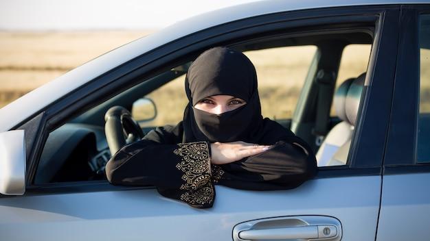 Портрет женщины за рулем автомобиля. мусульманка в национальной одежде