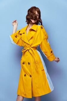 女性の肖像顔の毛楽しい黄色のコートスタイリッシュな服青い背景