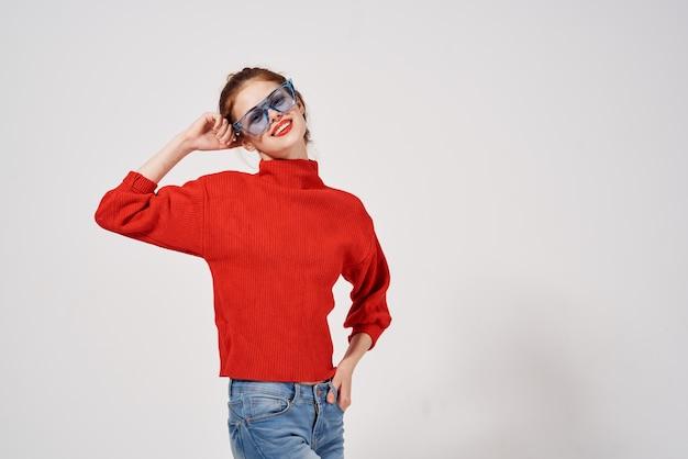 スタジオ楽しいモデルをポーズする女性のファッショナブルな青いメガネの肖像