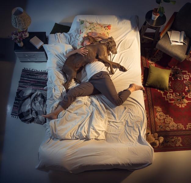自宅で犬と一緒にベッドで寝ている女性の女性ブリーダーの肖像画
