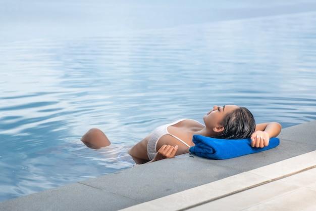 수영장에 떠 있고 수건에 그녀의 머리를 쉬고 여자의 초상화.