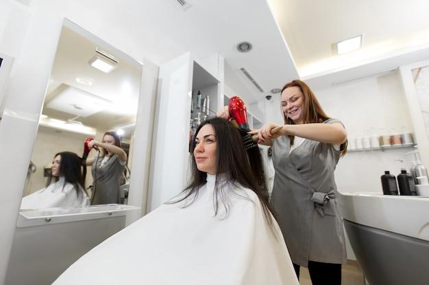 뷰티 살롱에서 클라이언트와 함께 작동하는 여자 미용사의 초상화. 미용사는 헤어 드라이어로 젖은 머리 소녀를 건조