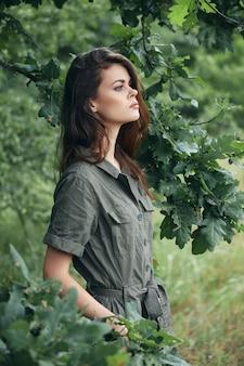 女性の肖像画ポケットに手を入れて緑の葉の側面図夏